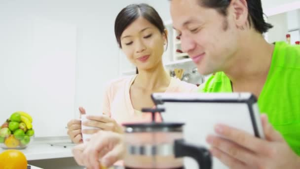Couple with wireless tablet at kitchen counter