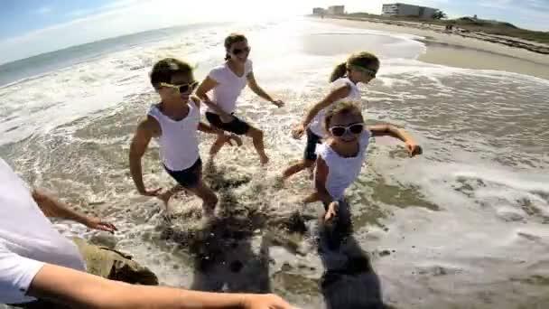 Family on beach filming self portrait