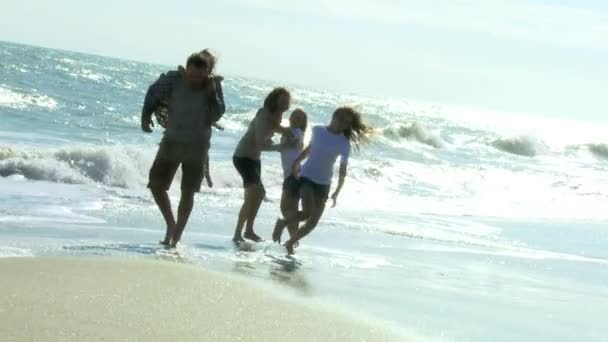 Girls playing with parents on beach