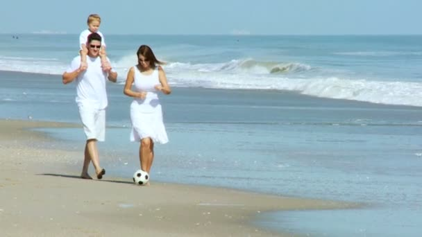 Parents with baby kicking ball on beach