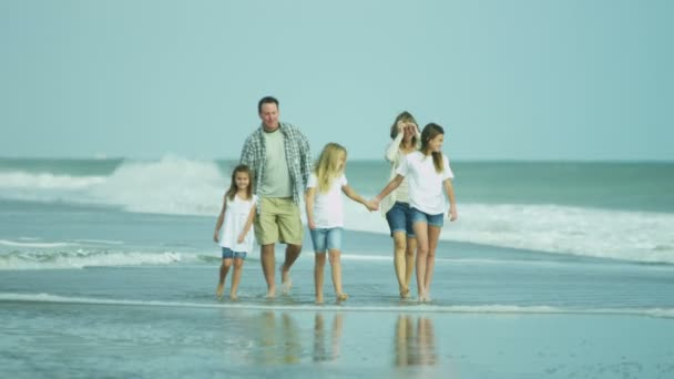 Parents with daughters walking on beach