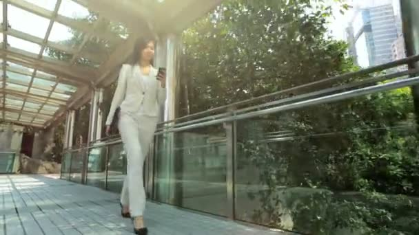 Businesswoman walking and using smartphone