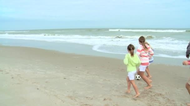 Family kicking ball on beach