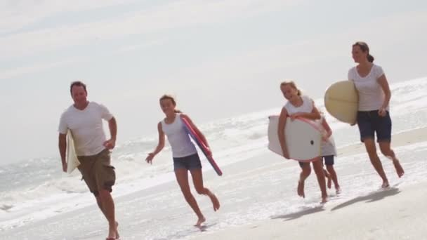 Parents with daughters running on beach