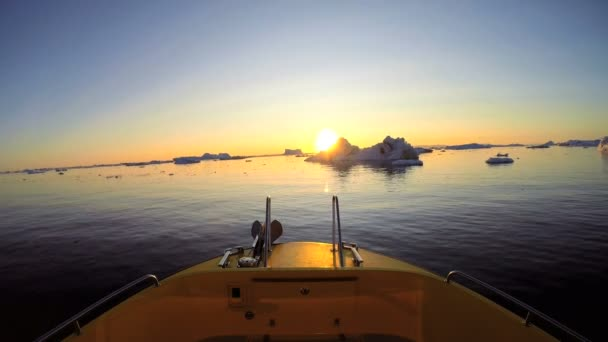 boat floating in the ocean with drifting icebergs