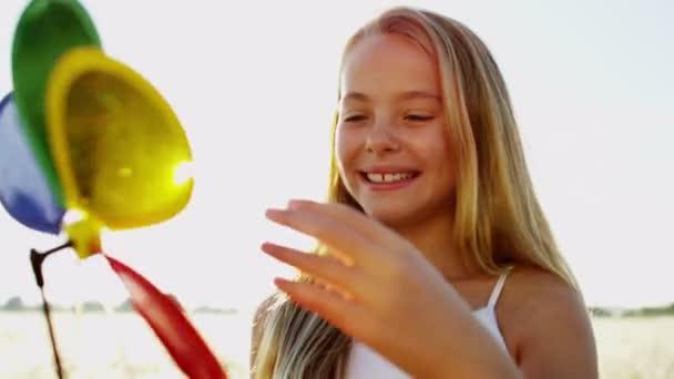 dívka si venku hraje s hračkou barevné větrný mlýn
