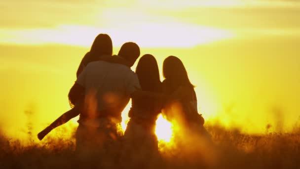 rodiče s dcerami na louce při západu slunce