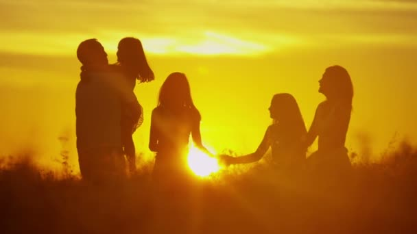 genitori con figlie sul prato al tramonto