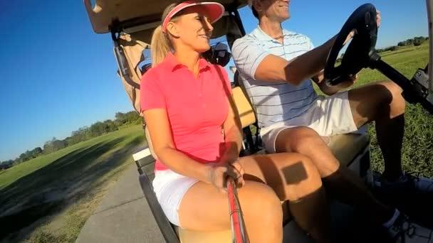 Dva hráči golfu, jízdy buggy vozík