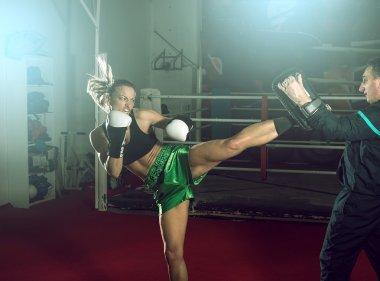 Girl doing high kick in kick boxing