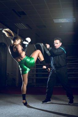 Boxing girl doing knee kick