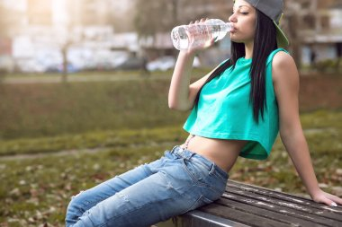 Roller girl drinking water on bench