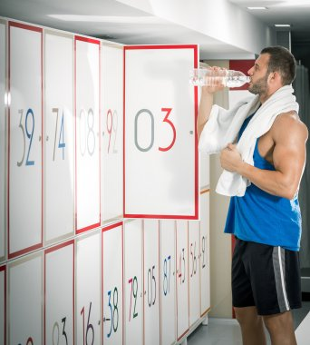 Young adult man drinking water in locker room