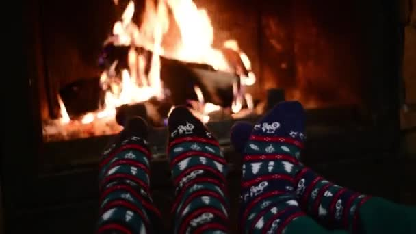Video of couple feet wearing in christmas socks warming by the burning fireplace