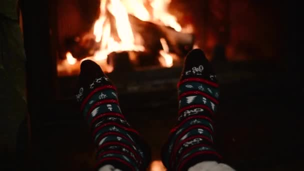 Man warms his feet by the fireplace, cozy home concept