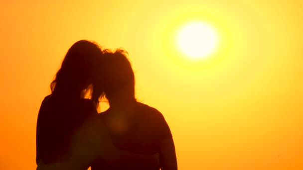Grown up daughter hugging mother while watching sunrise. Cinematic background of sunrise with two hugging girls. Romantic cinematic scene of girlfriend hugging woman on sunrise background. Back view