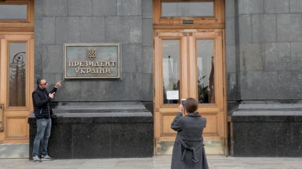 Touristen werden vor der Hintergrundtafel mit der Aufschrift - Präsident der Ukraine an der Tür des Haupteingangs zur Verwaltung des Präsidenten der Ukraine in Kiew fotografiert. Politik