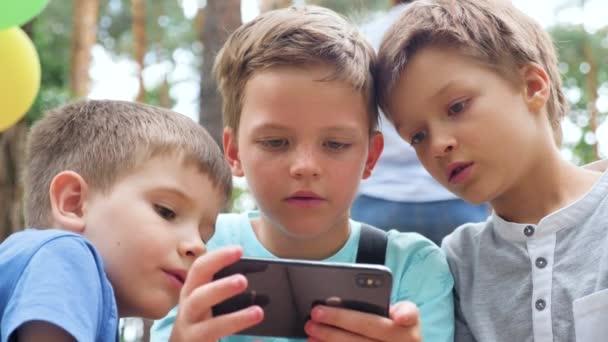 A gyerekek az okostelefonra koncentráltak. A gyerekek használják. Fiúk szórakozás okostelefon szabadban. Az okostelefonok generációja. Gyerekek és kütyü. Gyerekek játszanak kamattal videojátékok mobiltelefon a parkban