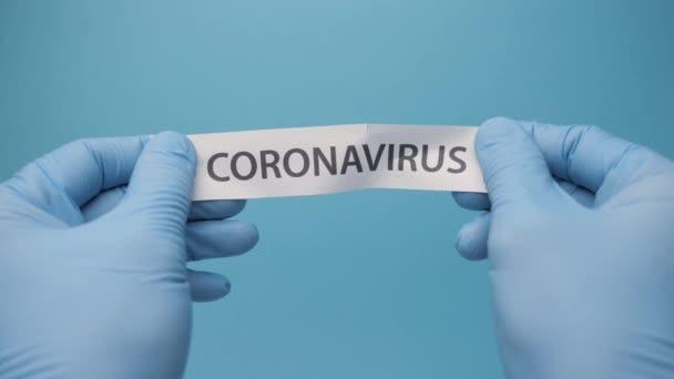 Ärzte reißen das Wort Coronavirus aus den Händen. Neuer Impfstoff stoppt Coronavirus-Ausbreitung Die Impfung kehrt nach der Pandemie Covid 19 zum normalen Leben zurück. Close up Reißen Papier Inschrift Coronavirus Text