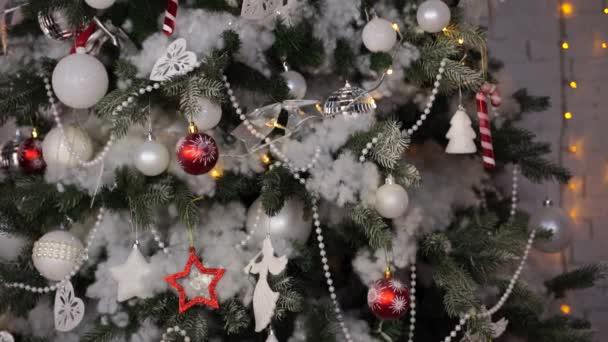 Zdobený vánoční stromek v pokoji. Jehličnatý strom s bílými a červenými cetkami umístěný u bílé zdi během svátků