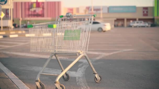 Grocery cart on parking in sunny weather. Empty abandoned shopping cart on street.