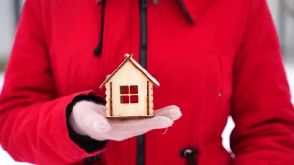 Zblízka ruku jedné ženy v rukavici držící malý dřevěný domek a druhou ruku ukazující palec nahoru v zimě. Koncept nákupu nového bytu.