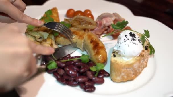 Nahaufnahme menschlicher Hand mit Gabel über verschiedenem Teller in weißem Teller. Appetitlich aus saftigen Würstchen, Bruschetta mit pochiertem Ei, roten Bohnen, Speck, Pilzen und Kirschtomaten im Restaurant.