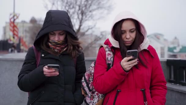 Close up of young women browsing smartphone in city park. Pretty females in hoods using mobile phone.
