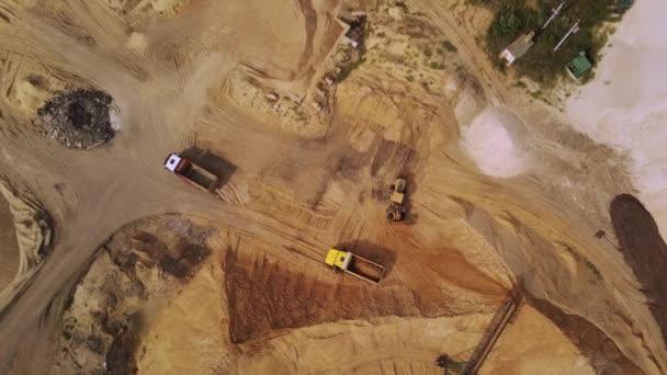 Gelber Bagger lädt Sand in die Mulde. Arbeit von Bagger und LKW im Sandbruch.