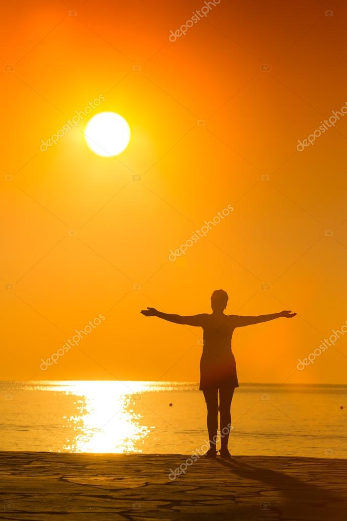 Silhouette of woman practicing yoga on the sunset