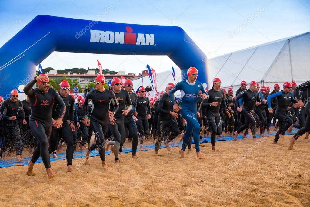 Calella, Spain, May 18. Triathletes run to water on start of the Ironman triathlon competition at Calella beach, May 18, 2014 in Calella, Spain