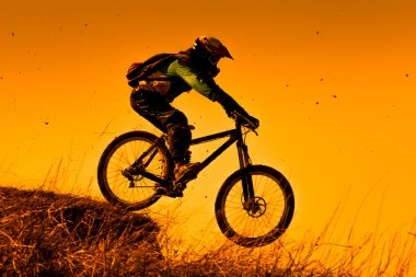 Downhill mountain bike ride at sunset