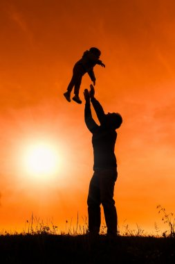 silhouette of father with baby flying over his head at orange sunset