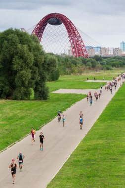 Triathletes run during triathlon competition in Moscow with cable-stayed red Jivopisny Bridge behind