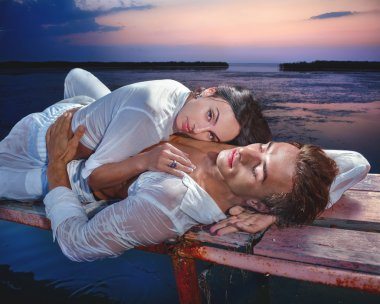 Couple lying on wooden jetty