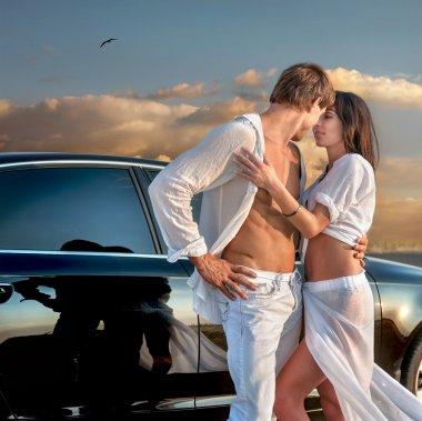couple in love near car at sunset