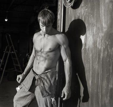 Young muscular guy near garage gate