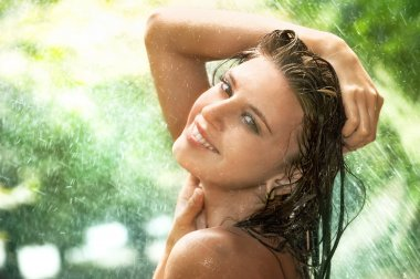 Young woman under summer rain