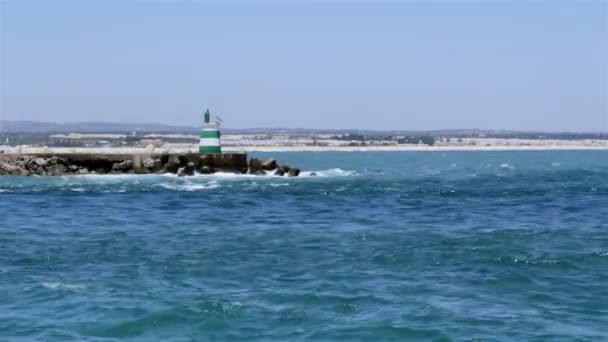 Ocean view of a inlet jetty small lighthouse and people surfing in Tavira Island, Algarve.