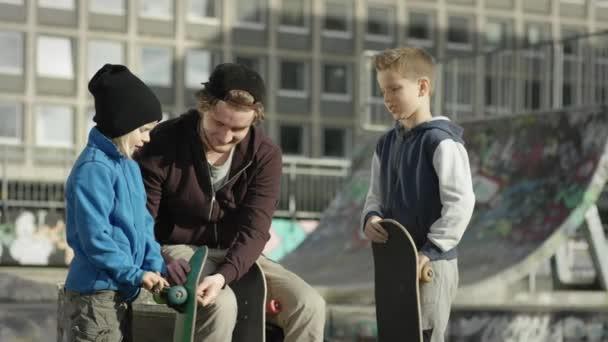 Chlapci a dospělého Probíhá oprava Skateboard