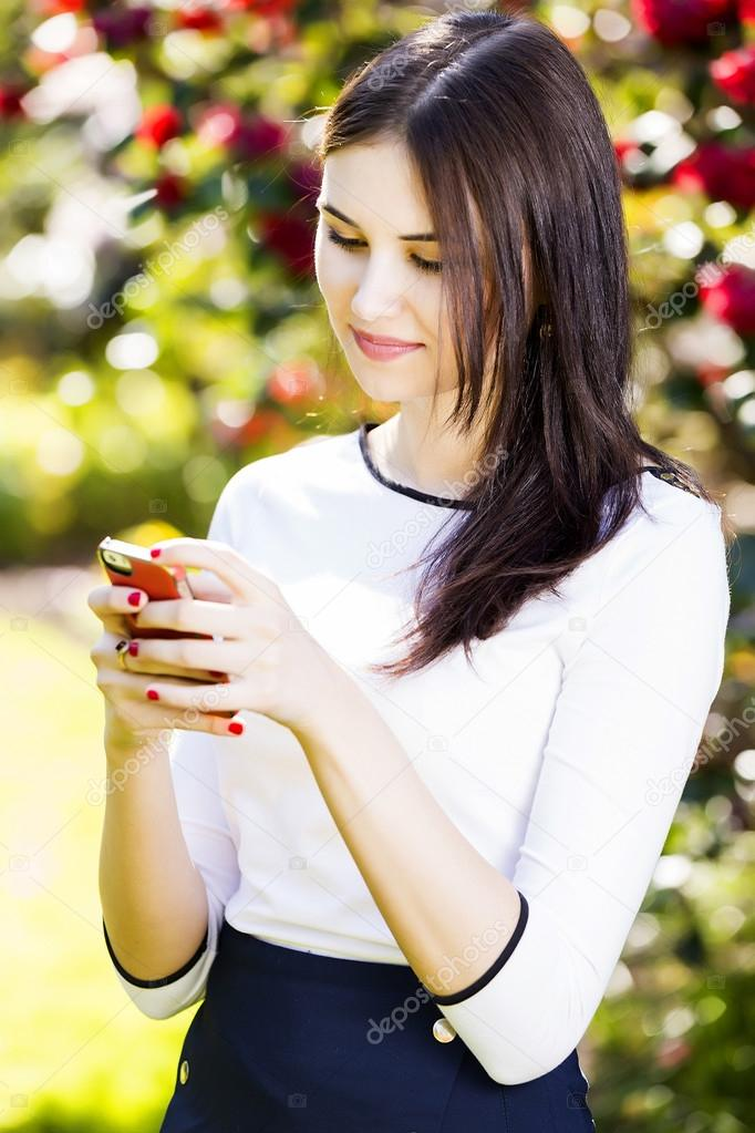 Beautiful Girl Typing Text Message On Her Smart Phone In The Gar