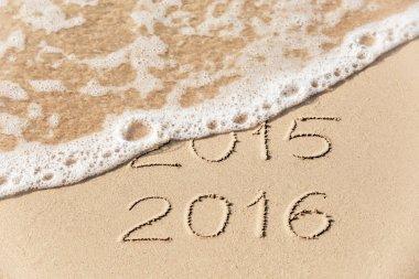 2015 2016 inscription written on the sand