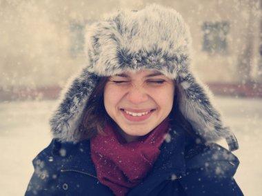 Cute funny girl in a fur cap laughing