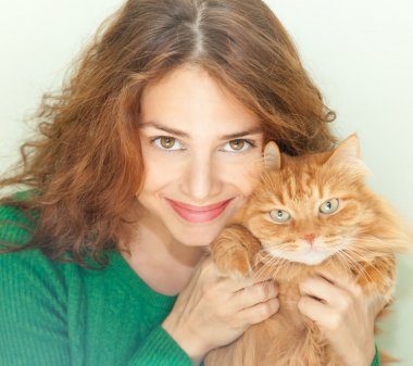 beautiful young woman with a red fluffy cat