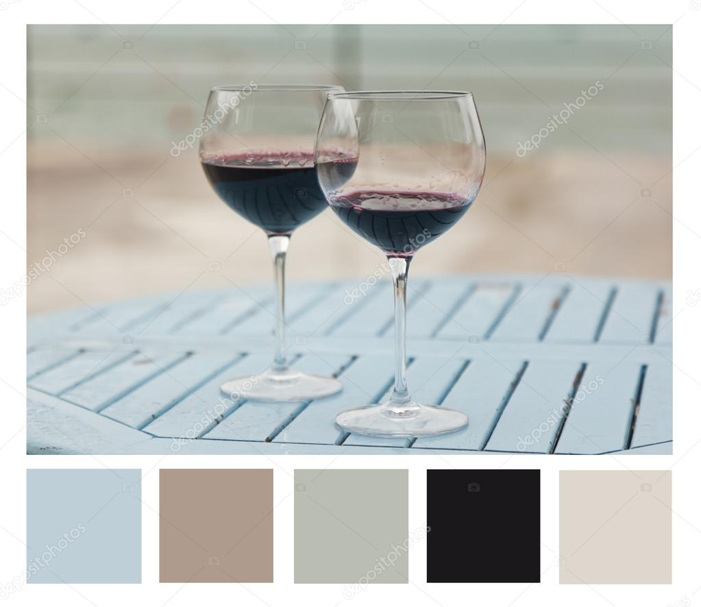 Two glasses with red wine on a table outdoor cafe, colour palett