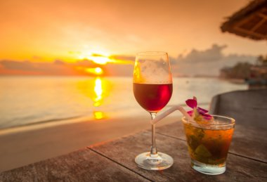 two glasses of wine on table on sunset