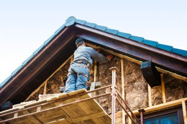 Construction worker thermally insulating house