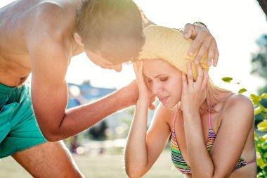 Man helping woman in bikini with heatstroke