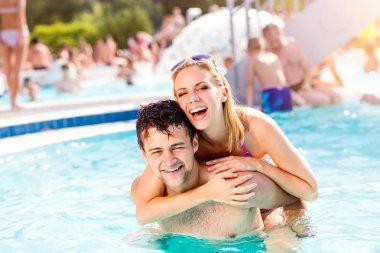 Couple in swimming pool, piggyback.