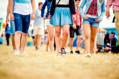 Unrecognizable teenagers at music festival walking, sunny summer, close up of legs stock vector